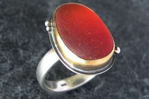 Red sea glass ring with gold bezel.